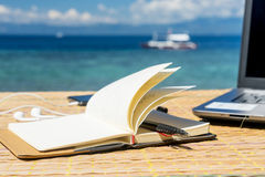 Opened empty notepad is on the table with phone and headphones at the tropical sea background Royalty Free Stock Image
