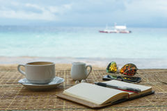 Opened empty notepad is on the table with sunglasses, phone, headphones at the background of tropical sea and philippine Stock Photos