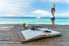Opened empty notepad is on the table with sunglasses, phone, headphones at the background of tropical sea and relaxing Royalty Free Stock Image