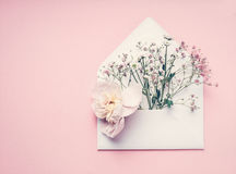 Opened Envelop With Flowers Arrangement On Pastel Pink Background, Top View, Copy Space. Creative Greeting, Invitation