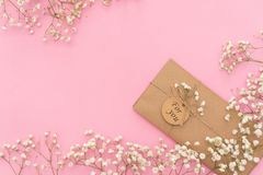 Opened envelope with Peonies flowers arrangements on pink background, top view. Festive greeting concept stock images