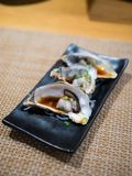 Opened fresh oysters on black plate royalty free stock photography