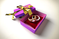 Opened gift box with a golden ribbon, two precious rings. Royalty Free Stock Photo
