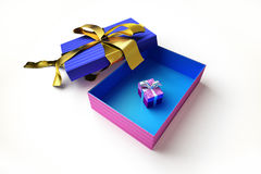 Opened gift box with a golden ribbon, on white surface. Stock Photos