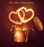 Opened gift-box with hearts. Opened gift-box with two hearts blow-up on dark with flame burning inside Stock Photo