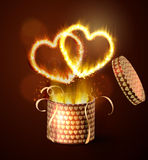 Opened gift-box with hearts. Opened gift-box with two hearts blow-up on dark with flame burning inside Royalty Free Stock Photography