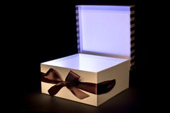 Opened gift box with inner light. Gift box on brown background Stock Photos
