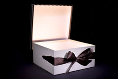 Opened gift box with inner light. Gift box on black background Royalty Free Stock Photo