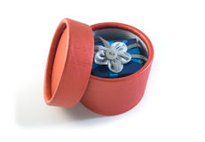 Opened gift box with surprise in it. Opened round red gift box with surprise in it: blue little box with rag flower Stock Images