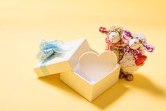 Opened gift box with white heart inside and couple sheep doll. On orange color background Stock Photo