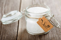 Opened glass jar with salt. Royalty Free Stock Image