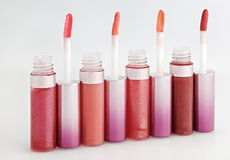 Opened gloss for lips set with color brushes. On white, arranged in line perspective Royalty Free Stock Image