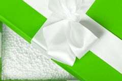 Opened green fancy box filled with white styrofoam balls. Packin. G for fragile present. Close shot Stock Photography