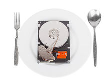 Opened hard drive disk on a white plate with a fork and spoon Stock Images