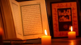 An opened holy Quran and a bible in back, candles in front stock footage