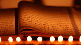 An opened holy Quran wiht candles in front, dolly shot stock footage
