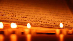 An opened holy Quran wiht candles in front, dolly shot stock video