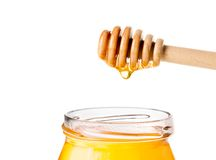 Opened honey jar on white background with wooden honey dipper on top with drop honey Royalty Free Stock Photography