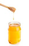Opened honey jar on white background with wooden honey dipper on top and drop honey Stock Photography