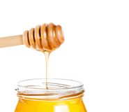 Opened honey jar on white background with wooden honey dipper on top pouring honey Royalty Free Stock Images