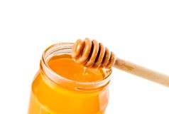 Opened honey jar on white background with wooden honey dipper on top pouring honey Stock Photography