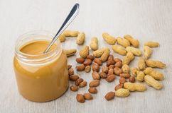Opened jar with peanut butter and teaspoon, scattered peanuts. On wooden table Stock Photography