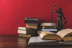 Opened juridical books with lady justice statue on wooden table,. Law concept stock photo