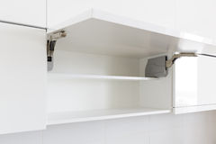 Opened kitchen cabinet. Opened white kitchen cabinet with empty shelf stock images