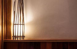 Opened lamp made of branch on wooden head bed and white wall, with copy space Royalty Free Stock Photo