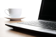 Opened lap top in front of coffee cup. Stock Images