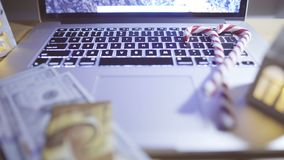 Opened laptop with blinking candles on table. Winter shopping. Sliding video of opened laptop with winter decor and us paper currency with credit card stock footage