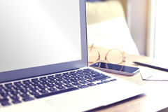 Opened laptop computer with blank screen space for design layout. Focus on screen corner. Mobile phone, glasses. Business still li Stock Photos