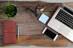 Opened laptop, smart phone, glasses, notebook and keys. Workspace concept. Stock Photos