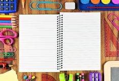 Opened lined school notebook with school supply frame on wood Royalty Free Stock Photo