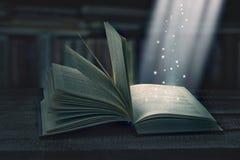 Opened magic book with magic light Stock Photos