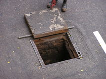 Opened manhole. On a road, a pair of feet can be seen next to it stock images