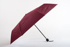 Opened maroon umbrella  on white background Royalty Free Stock Photography