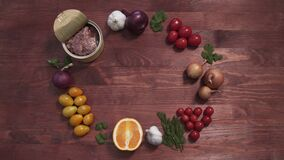 Opened Meat tin can served with vegetables and fruits, top view of a wooden table shot. Opened Meat tin can served with vegetables and fruits, top view of a stock video