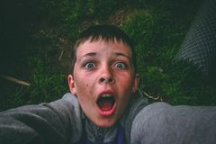 Opened Mouth Black Haired Boy in Gray Full-zip Jacket Standing on Grass Field Taking Selfie Stock Photos