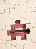 Opened mouth through puzzles Stock Photography