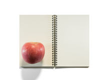 Opened note book with apple Royalty Free Stock Photography