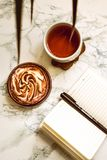 Opened notebook with blank area, pen and a cup of black tea on a white marble table in morning time.  stock images