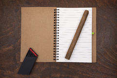 Opened notebook, cigar and matches. Opened notebook, cigar and matches on the old table Royalty Free Stock Photography