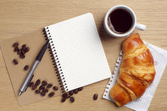 Opened notebook, croissant and coffee Royalty Free Stock Image