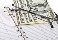 Opened notebook, dollars and glasses Stock Photo