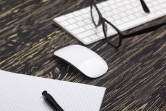 Opened notebook, glasses ,mug , modern computer keyboard and white mouse Stock Photo