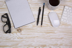 Opened notebook, glasses ,mug , modern computer keyboard and white mouse Royalty Free Stock Photos
