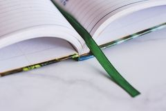 Opened notebook with green ribbon bookmark on white marble background stock image