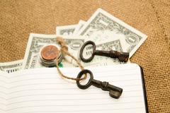 Opened notebook, key and money on the old tissue Royalty Free Stock Photos
