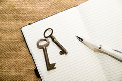 Opened notebook, keys and pen on the old tissue Royalty Free Stock Image